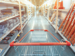 Abstract blurred photo of hardware store with empty shopping cart.
