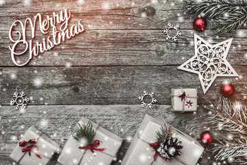 Christmas greeting card of horizontal shape, on old wooden background. Gifts and handmade toys. Space for text. Top view. Effect of light and snow