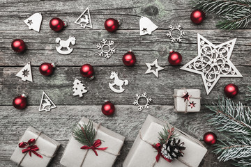 Christmas greeting card of horizontal shape, on old wooden background. Gifts and handmade toys. Top view.