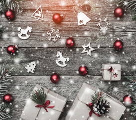 Christmas card of square shape, on old wooden background. Gifts and handmade toys. Space for text. Top view. Effect of light and snow