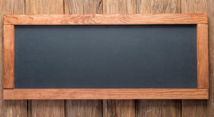 Blackboard on wooden background.