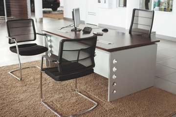Modern office interior: a table, two chairs and a laptop.