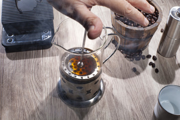 Barista doing french press with a bucket of coffee beans and scalling device with grinder and an empty cup on wooden table. Isolated on coffee drink maker concept.