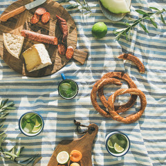 Autocollant pour porte Pique-nique Flat-lay of summer picnic set with fruit, cheese, sausage, bagels and lemonade over striped blanket, top view, square crop