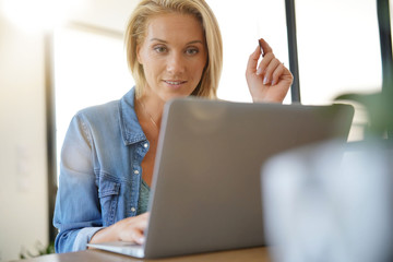 Blond woman at home shopping online