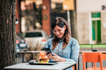 Young woman taking a picture of delicious hamburger before eating.