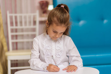 A cute little girl is sitting at a table drawing and telling.