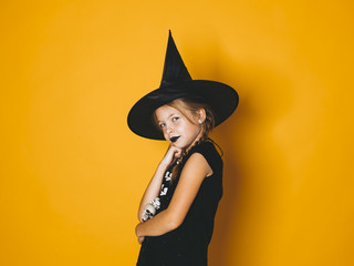 young halloween witch on orange background with black hat