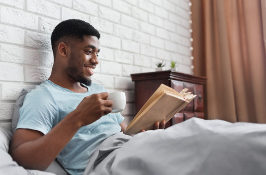 Black man drinking coffee and reading book in bed