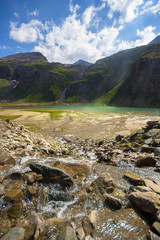 Standing in the center of a wild mountain creek, flowing in rivulets into the Nassfeldspeicher Lake, a so called power place, with sun rays enlightening the water surface, in the High Tauern, Austria