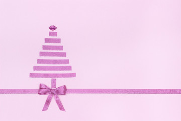 christmas tree and lips from decorative shiny ribbon with bow on pastel pink