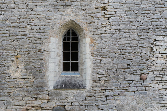 Window in the stone wall of an ancient monastery destroyed during the Livonian War in the Middle Ages