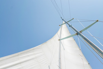 White sail of a sailing boat against sky. Sails of river sailing yacht in the wind against the blue sky