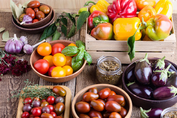Colorful vegetables on rural wooden table, bell peppers, eggplants and tomatoes