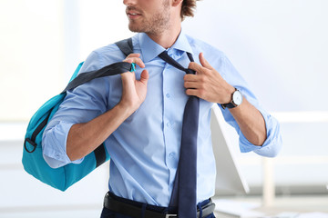 Young handsome businessman holding fitness bag in office. Gym after work
