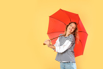 Wall Mural - Woman with red umbrella on color background