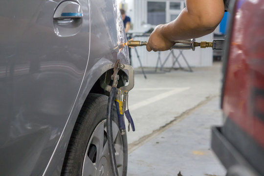 Mechanic's hands fix dents on the car's body with a special vacuum device