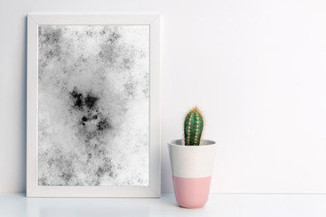 Marble graphics in a white frame and a cactus in a pink pot on a shelf