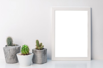 White empty mockup frame with cacti in concrete pots on the shelf