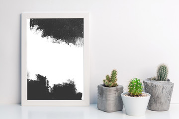 White framed black painted graphics and cacti in concrete pots on a white desk