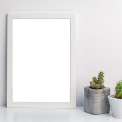Cactuses in concrete pots and empty mockup frame on white wall background