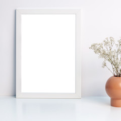 White mockup frame and white dried wildflowers in a brown vase on a shelf