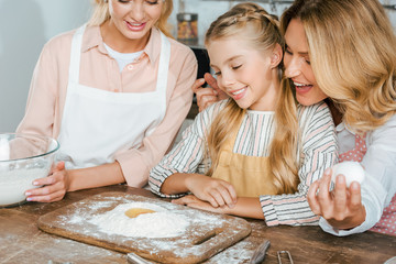close-up shot of little child with mother and grandmother making dough with flour and egg together at home