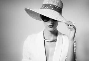 Fashion portrait of attractive female wearing hat and sunglasses.