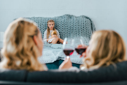 sad lonely child sitting on bed with toy while her mother clinking glasses of wine with friend on foreground