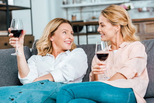 happy mature mother and adult daughter with glasses of red wine spending time together at home