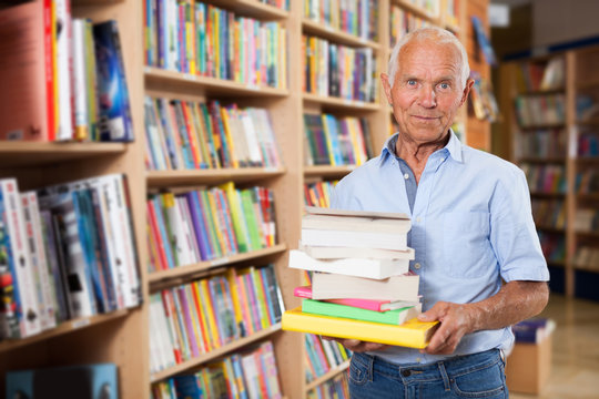 Elderly male buyer with pile of literature books in bookshop