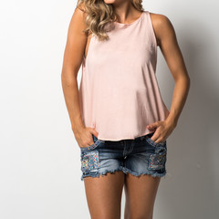 Woman in pink tank top and denim shorts