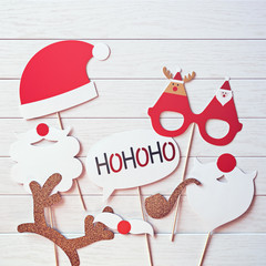 """A Christmas props for a photo booth (a Santa Claus hat, his beard or mustache, funny glasses, golden deer antlers, a smoking pipe, the phrase """"hohoho"""") is on a white wooden background.  Flat lay"""