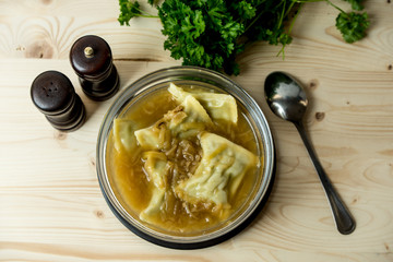maultaschen, German, traditional dumplings in a bowl with onion soup, next to fresh parsley, salt shaker and pepper pot
