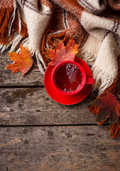 Autumn background with cup of tea, plaid and leaves