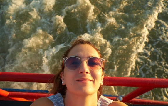 Woman in sunglasses on motor boat