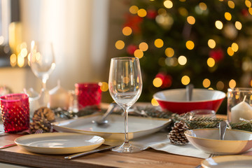 christmas, holidays and table setting concept - wine glass and tableware for festive dinner at home
