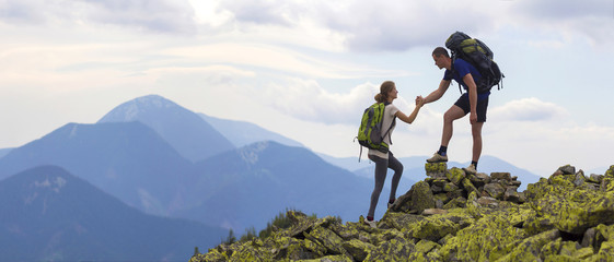 Papiers peints Alpinisme Young tourists with backpacks, athletic boy helps slim girl to clime rocky mountain top against bright summer sky and mountain range background. Tourism, traveling and healthy lifestyle concept.