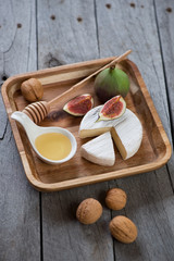 Camembert cheese with honey and figs on wooden serving tray, studio shot on a grey wooden table