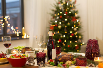 christmas dinner and eating concept - food and drinks on table at home