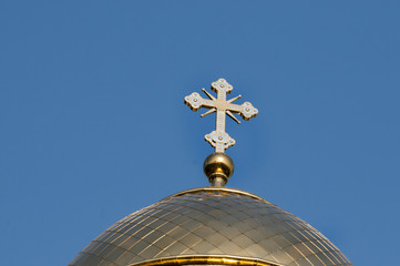 The golden dome and the cross of the Orthodox church against the blue sky and clouds.
