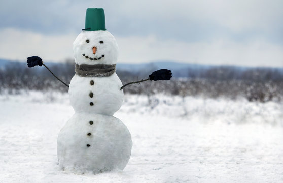 Big smiling snowman with bucket hat, scarf and gloves on white snowy field winter landscape, blurred black trees and blue sky copy space background. . Merry Christmas and happy new year greeting card.