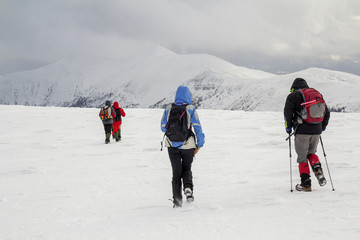 Winter mountain landscape. Three travelers tourist hikers in bright clothing with backpacks on snowy field walking towards distant mountain on cloudy dark blue stormy sky copy space background.