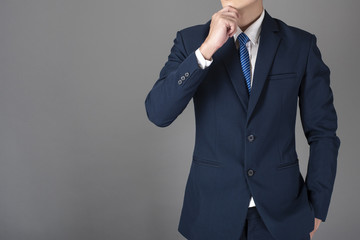 Close up of business man in blue suit is thinking on gray background