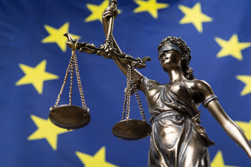 Statue of the blindfolded goddess of justice Themis or Justitia, against an European flag, as a legal concept Wall mural