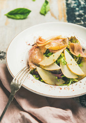 Fresh summer salad with smoked turkey ham and slices of pear in white plate over scorched rustic wooden table background, selective focus, vertical composition