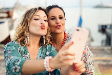 Two adult women have fun making grimaces while they make selfie outdoors.
