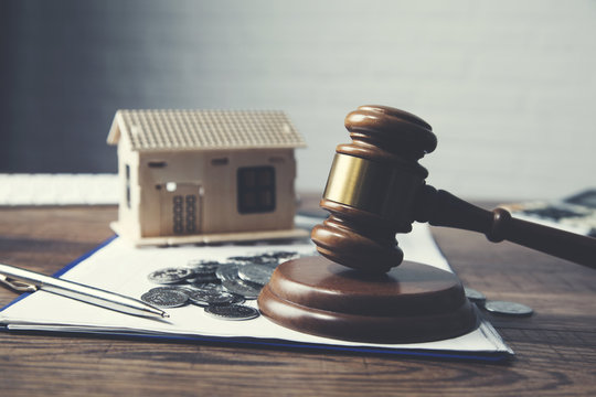 Gavel with house model and coins on table