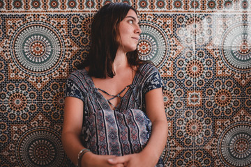 Young woman sitting near patterned wall
