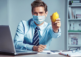 Healthy worker at the office holding lemon. Photo of man wearing protective mask against infectious diseases and flu. Business and health care concept.